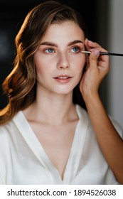 A beautiful young woman with long hair doing makeup for a wedding or photo shoot. the work of a make-up artist. the morning of the bride. decorative cosmetics.
