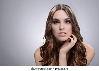 Beautiful young woman with long hair on grey background - Shutterstock ID 196355675