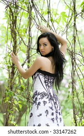 Beautiful young woman with long hair in foliage