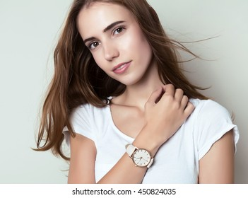 beautiful young woman with long hair posing in casual clothes and wearing a wrist watch