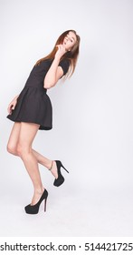 Beautiful young woman with long hair isolated on white. high-heeled shoes