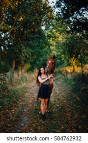 Beautiful young woman with long hair and slim figure,black skirt,fashion boots,vest and accompanied by their stallion. All around are fallen leaves,grass and trees gradually defocusing in background.