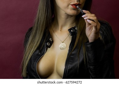 Beautiful young woman with long hair, red lips, smoking and wearing leather jacket with deep cleavage and no bra