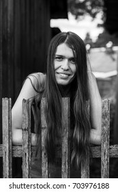 Beautiful young woman with long hair near a rustic wooden fence. Black-and-white photograph.