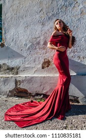 Beautiful young woman in a long red evening gown with a train standing next to the old wall. Copy space