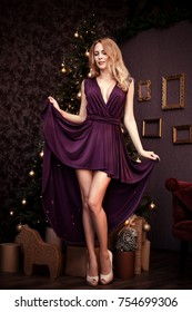 Beautiful young woman with long sexy legs and purple fashion dress asymmetric length stay near christmas decorated tree eve at home