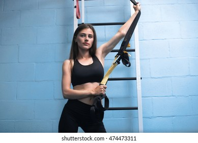 Beautiful young woman with long straight brunet hair wearing in blue shirt is doing exercises with TRX near the gray wall in gym