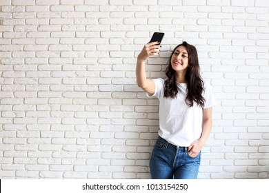 Beautiful young woman, long wavy brunette hair, dressed in 90s style, making selfie. Female wearing mom jeans & plain white t shirt taking pictures of herself. White brick wall background, copy space.