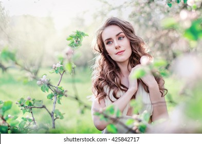 beautiful young woman in a long white dress with wavy hair in lush flowering garden