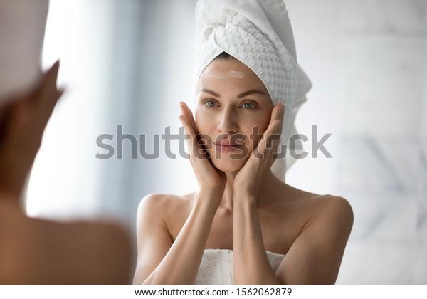 美しい若い女性が顔を鏡のマッサージで洗面し、クリームを塗ってお風呂に入れ、きれいな女性がタオルを頭の上に乗せ、保湿クリームを水に入れる保湿剤を持ち上げ、肌のケアのコンセプト