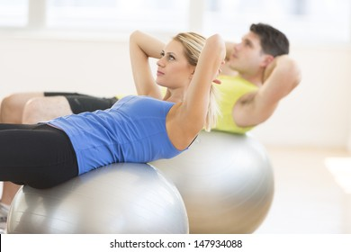 Beautiful young woman looking away while exercising on fitness ball with man in background at gym