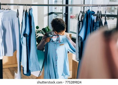 beautiful young woman looking at blue shirt at clothing store