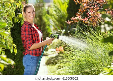 Beautiful young woman is looking at camera and smiling while watering plants in her garden with garden hose.
