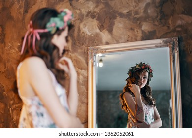Beautiful young woman looking at her reflection in the mirror.  Girl dressing concept