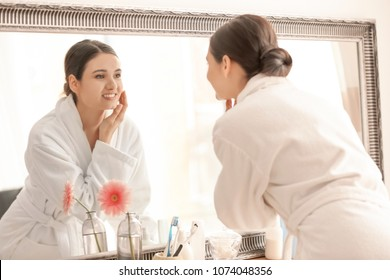 Beautiful young woman looking at herself in mirror indoors