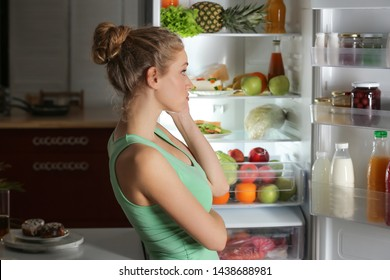 Beautiful young woman looking into fridge at night