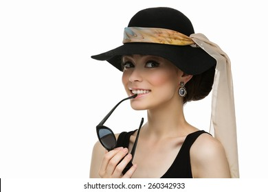 Beautiful young woman looking like Audrey Hepburn in hat with scarf and holding sunglasses