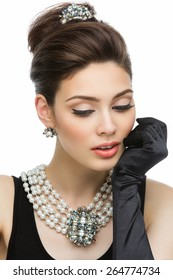 Beautiful young woman looking like Audrey Hepburn wearing pearls
