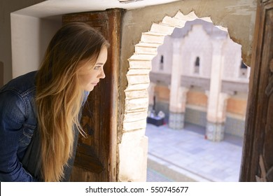 Beautiful young woman looking out of the window