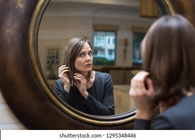 Beautiful young woman looking at self in big round mirror
