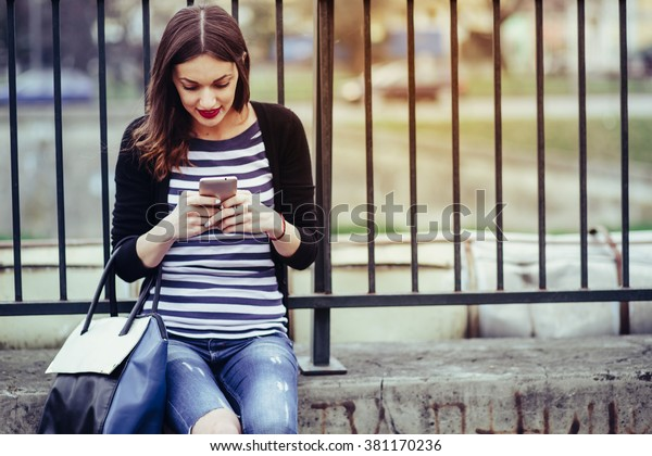 beautiful young woman looking at smar tphone in city/ young smiling woman looking at her smart phone