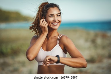 A beautiful young woman is looking at smartwatch and preparing to do jogging at the sea beach in summer sunny day.