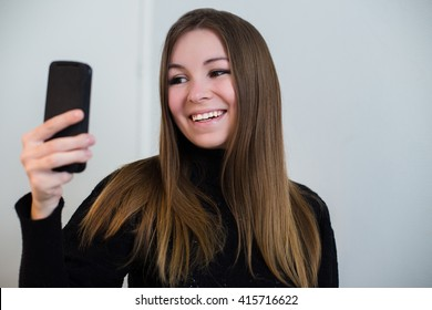 Beautiful young woman looking and smiling into the camera of her smartphone