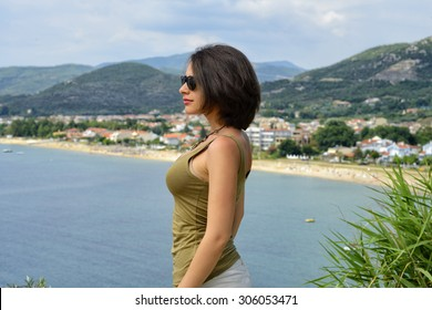 Beautiful young woman looking at sunny beach and mountain view