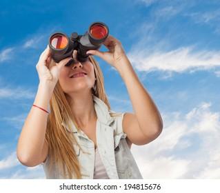 beautiful young woman looking through binoculars