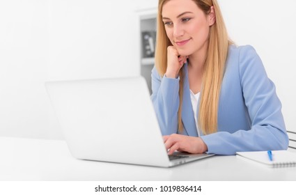 Beautiful young woman looks at the laptop monitor screen while sitting at the office desk. Beautiful blonde in blue in the workplace.