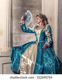 Beautiful young woman in the lush expensive dress with fan in an old palace interior. Vintage style. Renaissance. Barocco. Fashion. Fairy tale.