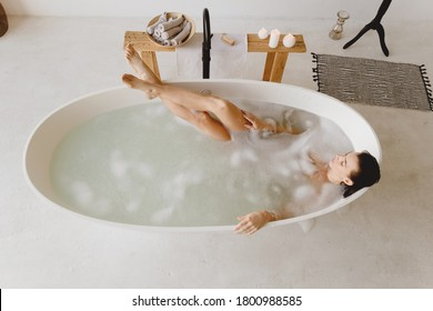 Schöne junge Frau, die in einer Badewanne mit Schaumstoff liegt. Draufsicht.