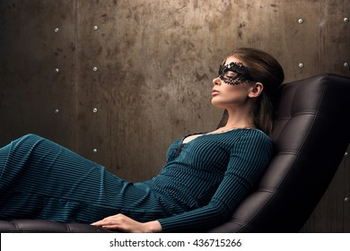Beautiful young woman lying in a chair with his eyes closed. Black lace mask on the eyes. Long green dress. Back in the loft