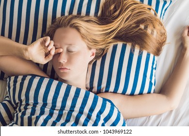 Beautiful young woman lying down in bed and sleeping. Do not get enough sleep concept