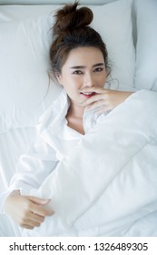 Beautiful young woman lying down in the bed and sleeping.