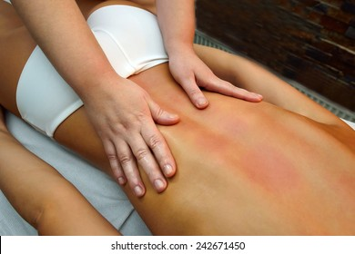 beautiful young woman lying down while massage therapist is  massaging her