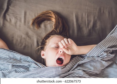 Beautiful young woman lying down in bed and sleeping, top view. Do not get enough sleep concept.