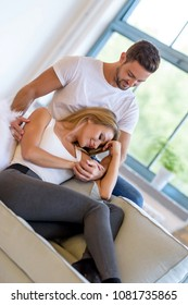 A beautiful young woman lying on the sofa with boyfriend hugging her from behind.