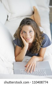 Beautiful young  woman lying on sofa with laptop