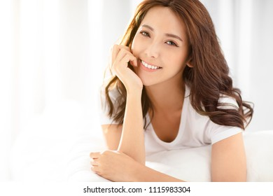Beautiful young woman lying on the bed and smiling