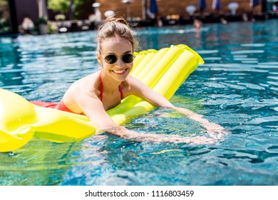 beautiful young woman lying on inflatable mattress in swimming pool and looking at camera