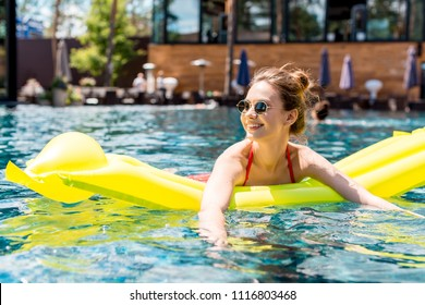 beautiful young woman lying on inflatable mattress in swimming pool and looking away