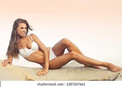 Beautiful young woman lying on a rock in a white bikini.