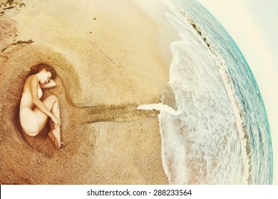 Beautiful Young Woman lying on Sea shore. Ocean as Abstract embodiment of Universe that Cares about People. Global Love concept