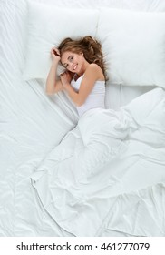 Beautiful young woman lying on bed