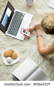 Beautiful young woman lying on white carpet with cup of tea and cookies, browsing social media, looking at pictures on smartphone and laptop, studying and relaxing at home. Close-up top view image