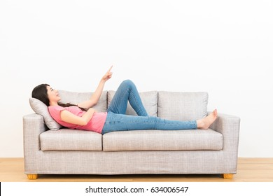 beautiful young woman lying on wooden floor sofa couch finger pointing gesture with white wall background in the living room.
