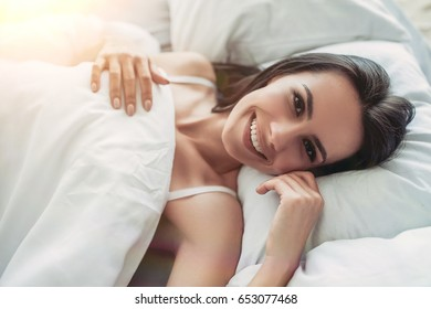 Beautiful young woman is lying on bed, smiling and looking at the camera