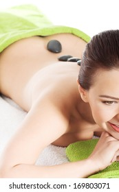 Beautiful young woman lying and relaxing during stone masasge. Spa concept.