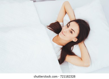 Beautiful young woman lying in white bed and dreaming